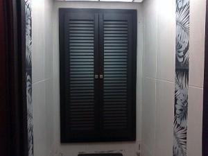Дизайнерское решение использования черных дверец для сантехнического шкафа в туалете