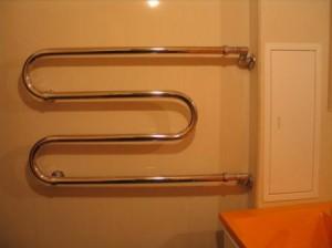 Установленный в ванной комнате водяной М-образный полотенцесушитель